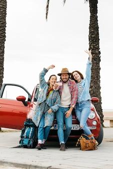 Mensen die selfie dichtbij rode auto nemen