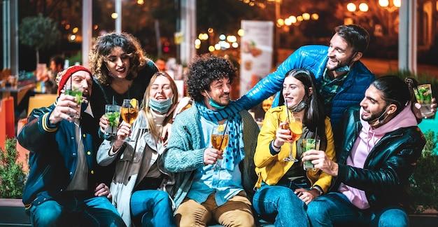 Mensen die spritz en mojito drinken bij cocktailbar die open gezichtsmasker dragen