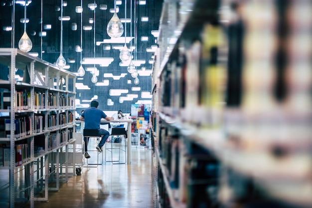 Mensen die studeren in de openbare moderne bibliotheek - man zit van achteren aan het werk op een computerlaptop - stadsruimte voor studenten om te leren en les te geven