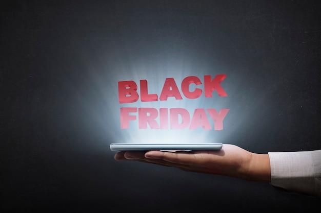 Mensen die tablet houden en advertentie van black friday tonen