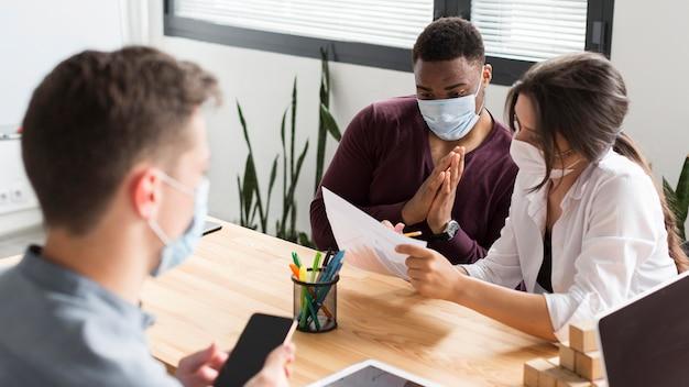 Mensen die tijdens een pandemie op kantoor werken met maskers aan