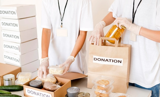 Mensen die voedseldoos en zak voorbereiden op schenking