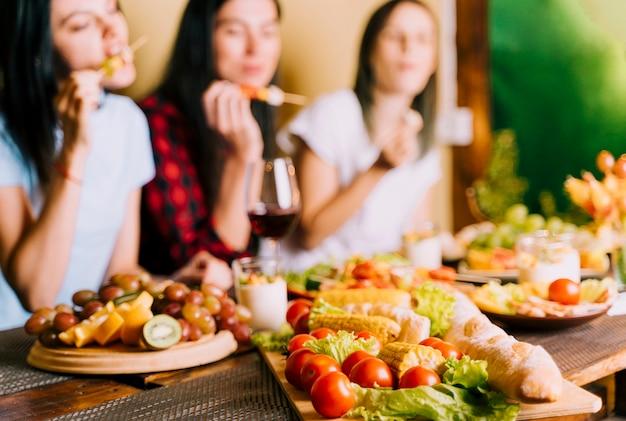 Mensen die voorgerechten vage achtergrond eten