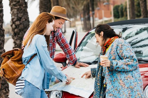 Mensen die wegenkaart dichtbij auto bekijken