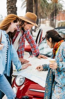 Mensen die wegenkaart dichtbij rode auto bekijken