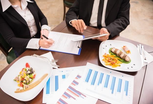Mensen die werken aan marketingstrategie tijdens zakelijke lunch.