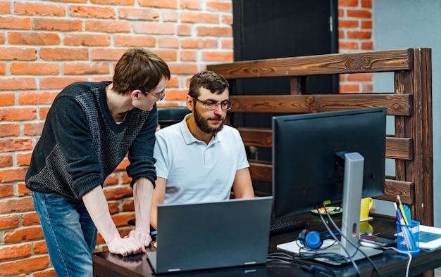 Mensen die werken en communiceren. twee zekere jonge mannen die laptop monitor bekijken