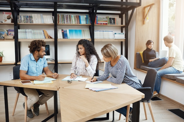 Mensen die werken in team. drie jonge perspectiefpartners die in bibliotheek zitten die op startprojectdetails en winsten bespreken. teamwerk concept.