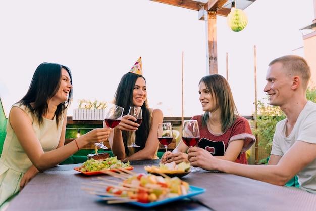 Mensen die wijn drinken en eten op verjaardagsfeestje