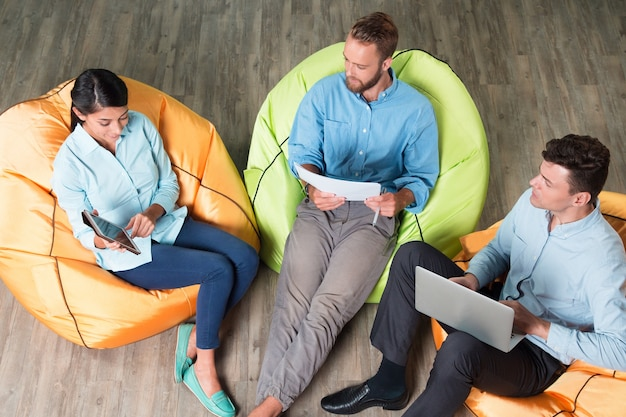 Mensen die zakelijke problemen bespreken op beanbag stoelen