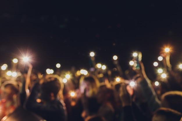 Mensen die zich met opgeheven wapens bevinden schieten een video op de telefoon bij een straatmuziekshow, vage achtergrond.