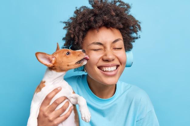 Mensen dieren relatie concept. gelukkige positieve gekrulde afro-amerikaanse vrouw poseert met huisdier dat samen buiten gaat lopen. kleine hond likt eigenaar op wang en drukt liefde uit om verzorgd te worden