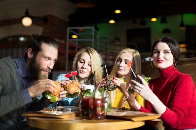 Mensen dineren samen aan een tafel in een café. gelukkige vrienden eten hamburgers en drinken cocktails in het restaurant.