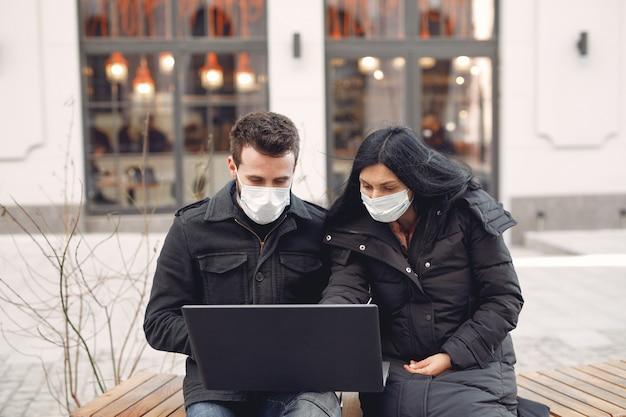 Mensen dragen een beschermend masker zitten in een stad met een laptop