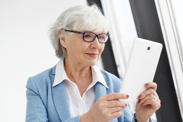 Mensen, elektronische gadgets, technologie en communicatieconcept. moderne slimme volwassen senior vrouw ondernemer in stijlvol pak en rechthoekige bril met digitale tablet, surfen op internet
