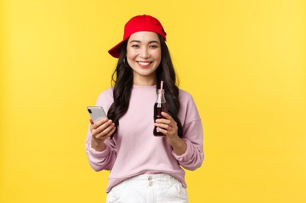 Mensen emoties, drankjes en zomer vrije tijd concept. jonge koreaanse tienermeisje in rode dop, berichten verzenden, smartphone gebruiken en frisdrank drinken, staande gele achtergrond tevreden.