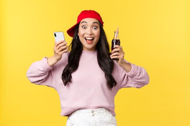 Mensen emoties, drankjes en zomer vrije tijd concept. opgewonden en enthousiast mooi aziatisch tienermeisje dat zich verheugt over nieuwe frisdranksmaak, drankje aanbevelen, mobiele telefoon en fles vasthoudt Gratis Foto