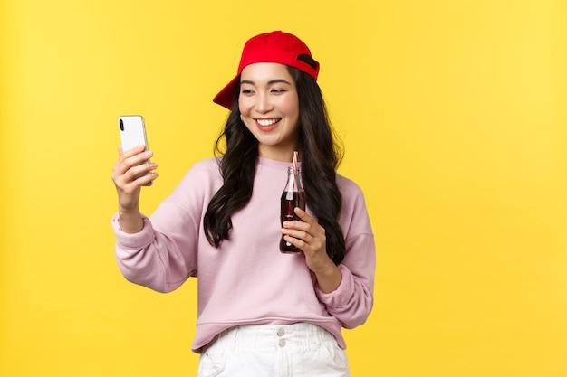 Mensen emoties, drankjes en zomer vrije tijd concept. stijlvolle schattige aziatische vrouwelijke blogger in rode dop, selfie nemen met smartphone, frisdrank drinken en zichzelf fotograferen.