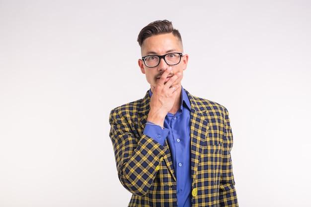 Mensen, emoties en gebaar concept - jonge verraste man die zijn mond bedekt met zijn hand op een witte achtergrond.