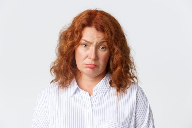 Mensen, emoties en levensstijlconcept. ongeamuseerde vermoeide roodharige vrouw van middelbare leeftijd die droevig gezicht maakt en camera terughoudend bekijkt, die somber over witte achtergrond staat. kopieer ruimte