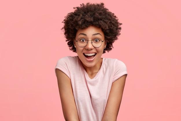 Mensen, emoties en prettige gevoelens concept. mooie jonge afro-amerikaanse vrouw met vrolijke expressie, lacht gelukkig als grappige programma horloges tijdens vrije tijd, draagt casual t-shirt