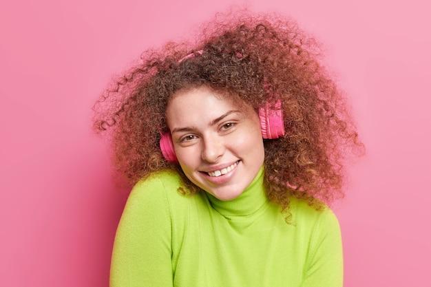 Mensen emoties hobby concept. positieve cury haired tienermeisje glimlacht graag uitdrukking van vreugde draagt draadloze koptelefoon op oren geniet van luisteren muziek draagt groene trui geïsoleerd op roze muur