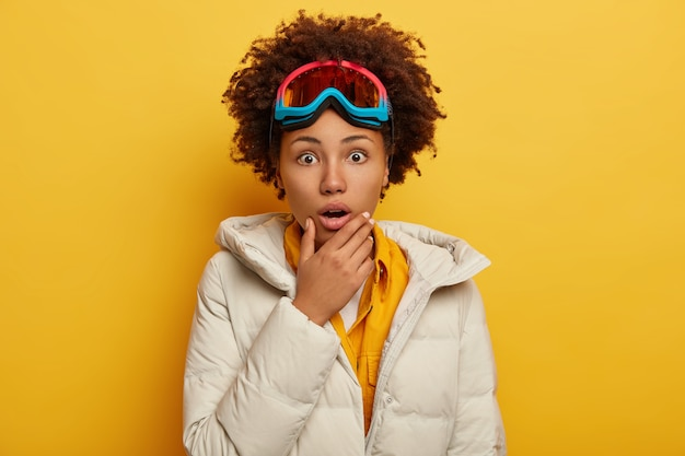 Mensen, emoties, hobby en vrije tijd concept. angstige emotionele krullende afro-amerikaanse vrouw draagt een snowboard masker, gekleed in een gezwollen witte jas, houdt kin
