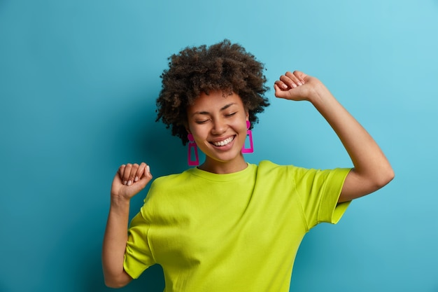 Mensen, emoties, levensstijl en vrijetijdsconcept. vrolijk vrolijk vrouwelijk model met donkere huid danst met de handen omhoog, heeft plezier en feesten, beweegt met het ritme van de muziek, heeft een gelukkige glimlach, geïsoleerd op blauwe muur