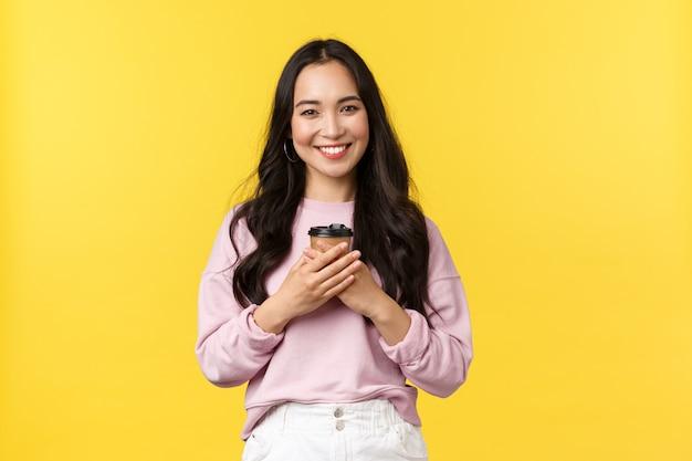 Mensen emoties, levensstijl vrije tijd en schoonheid concept. mooie aziatische vrouw die met kop van meeneemkoffie van de zomerweekenden genieten, opgetogen en leuk glimlachen, drank drinken over gele muur