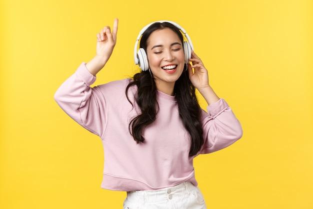 Mensen emoties, levensstijl vrije tijd en schoonheid concept. vrij gelukkig aziatische vrouw in draadloze hoofdtelefoons, muziek luisteren en dansen, meezingen, genieten van de zomer