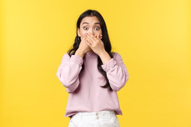 Mensen emoties, lifestyle en mode concept. geschokt en geschrokken aziatische vrouw die verbaasd is over groot nieuws, drukt de handen voor de mond en verwijdt de ogen verbaasd, staande gele achtergrond.