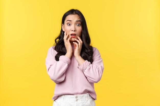 Mensen emoties, lifestyle en mode concept. geschokte en bezorgde onzekere aziatische vrouw reageert op slecht schokkend nieuws, hijgend en ontroerend gezicht, staren angstig naar de camera, gele achtergrond.