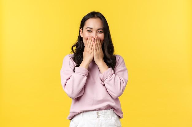 Mensen emoties, lifestyle en mode concept. grappige en schattige koreaanse vrouw die verlegen lacht, lacht met ogen terwijl ze de mond bedekt en giechelt dom naar de camera, staande op een gele achtergrond.