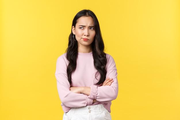 Mensen emoties, lifestyle en mode concept. verontruste en twijfelachtige aziatische vriendin met bezorgde gedachten, kijkend in de linkerbovenhoek en grimassen, peinzende, gele achtergrond.