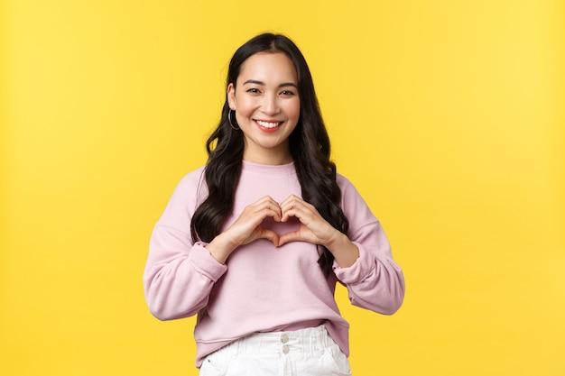 Mensen emoties, lifestyle en mode concept. vriendelijke en schattige vrouw van gemengd ras in vrijetijdskleding, die over een gele achtergrond staat, een hartteken toont en gelukkig glimlacht.
