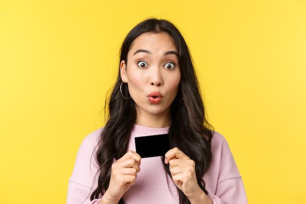 Mensen emoties, lifestyle vrije tijd en schoonheid concept. geamuseerd opgewonden aziatisch meisje met creditcard, starende camera als klaar om alles in de winkel te kopen, winkelen voor zomervakantie.