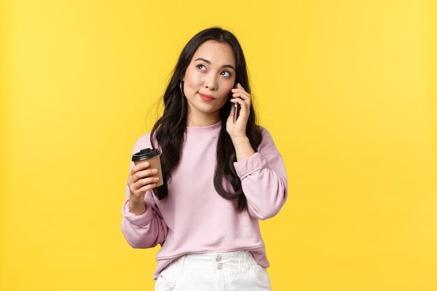 Mensen emoties, lifestyle vrije tijd en schoonheid concept. leuke stijlvolle aziatische vrouw die attent opkijkt terwijl ze op mobiele telefoon praat en koffie drinkt uit een afhaalbeker, gele achtergrond.