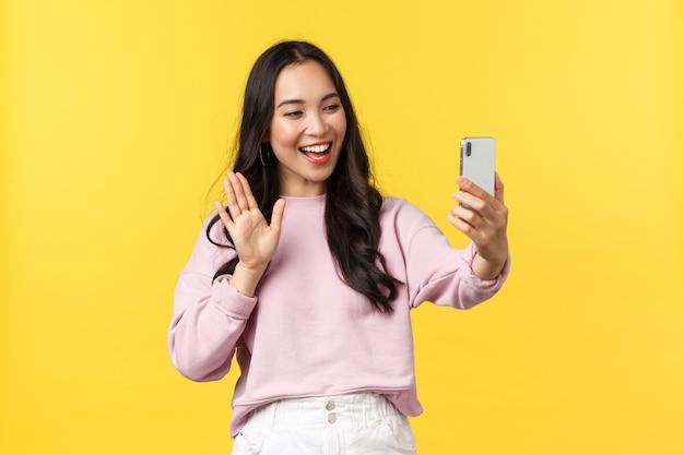 Mensen emoties, lifestyle vrije tijd en schoonheid concept. schattig extravert aziatisch meisje dat op videocall praat met vrienden, met de hand zwaait om hallo te zeggen op de telefooncamera, blogger heeft livestream, gele achtergrond.