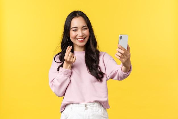 Mensen emoties, lifestyle vrije tijd en schoonheid concept. vrolijk aziatisch meisje over gele achtergrond die selfie op mobiele telefoon neemt, app voor fotofilters gebruikt en hartgebaar toont.