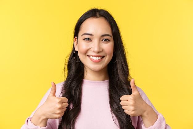 Mensen emoties, lifestyle vrije tijd en schoonheid concept. vrolijk lachend aziatisch meisje met duim omhoog in goedkeuring, staande gele achtergrond, akkoord gaan en ondersteunen idee, gele achtergrond.