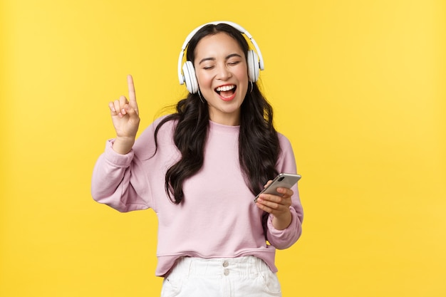 Mensen emoties, lifestyle vrije tijd en schoonheid concept. zorgeloze gelukkige aziatische vrouw die muziek luistert in draadloze koptelefoons, mobiele telefoon vasthoudt, meezingt met favoriete liedje, gele achtergrond.