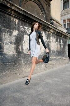 Mensen, emoties, natuurlijk, schoonheid en lifestyle concept - jonge mooie vrouw in jurk en leren jas staande op het dak in de buurt van hek