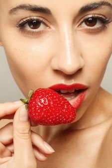 Mensen, emoties, natuurlijk, voedsel, schoonheid en levensstijlconcept - sexy vrouw die aardbei eet. sensuele lippen. manicure en lippenstift. verlangen. schoonheid meisje sexy lippen met aardbei. witte tanden