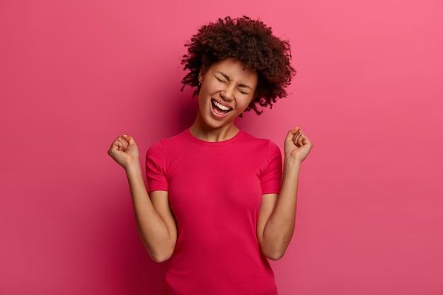 Mensen, emoties, triomf en succesconcept. gelukkig afro-amerikaanse tienermeisje viert overwinning, steekt vuisten op, heeft een vrolijke bui, gekleed in vrijetijdskleding, geïsoleerd op een roze muur.