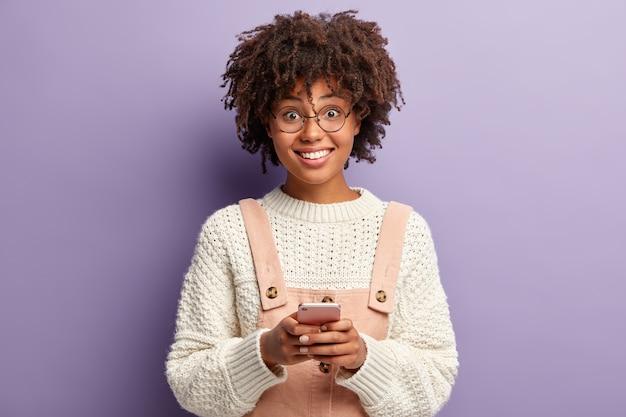 Mensen en communicatieconcept. glimlachend donkerhuidig tienermeisje surft sociale netwerken op mobiele telefoon, zoekt hilarische video, heeft een blije blik