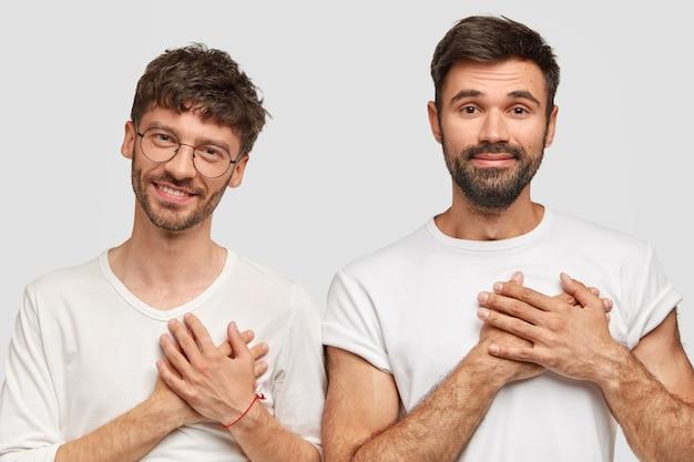 Mensen en dankbaarheid concept. dankbare tweemansstudenten die graag goede cijfers halen voor het examen, baard en snor hebben, gekleed in een casual wit t-shirt