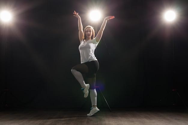 Mensen en dansen concept - mooie vrouw jazz funk dansen over donkere achtergrond.