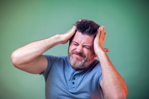 Mensen en emoties - een portret van een man die aan iets denkt en hoofdpijn voelt