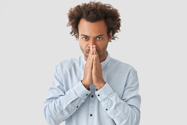 Mensen en geloofsconcept. knappe jonge ernstige afro-amerikaanse man houdt de handen in het bidden gebaar, ziet er zelfverzekerd uit, gekleed in een wit overhemd, is sterk van mening dat zijn dromen uitkomen.