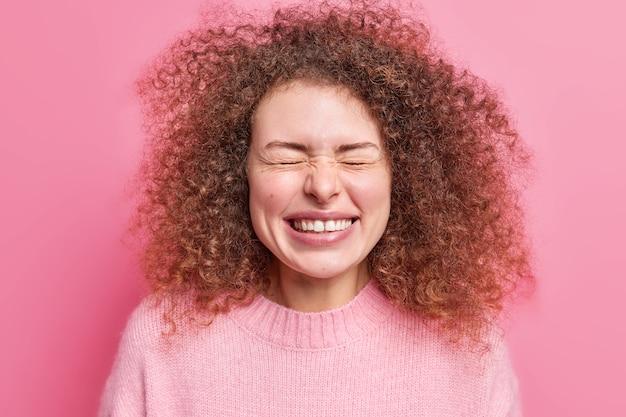 Mensen en geluk concept. blij dat jonge europese vrouw met krullend haar glimlacht, voelt zich in het algemeen erg gelukkig, sluit de ogen en loenst gekleed in een casual trui geïsoleerd over roze muur.